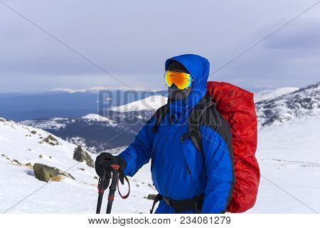Mountaineer In Mirror Wind-proof Glasses And A Windproof Mask With A Backpack On A Background Of A W