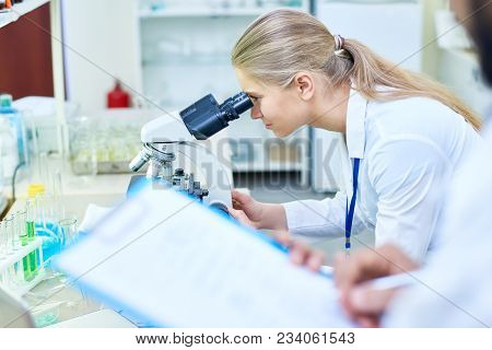 Concentrated Young Female Biologist Looking Through Microscope While Analyzing Sample In Modern Labo