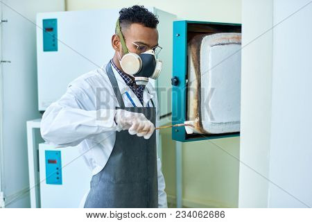 Concentrated Arabian Scientist In Respirator Carrying Small Hot Cup To Put It Into Furnace And Exami