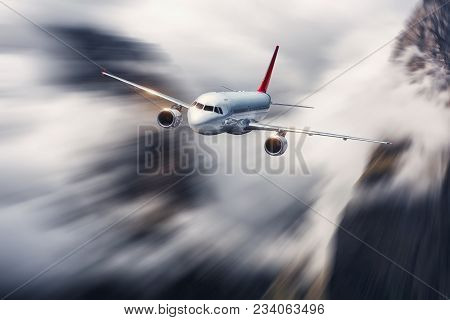 Airplane In Motion. Aircraft With Motion Blur Effect Is Flying In Clouds Against Mountains. Passenge
