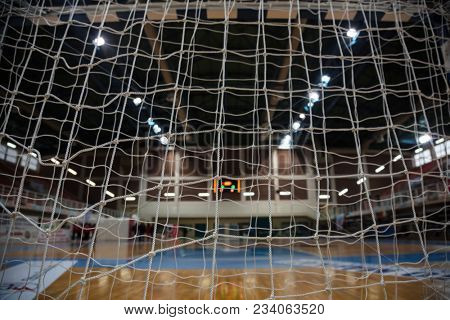 Handball concept. Close up goal post nets from behind view. Blurred court, athletes and electronic scoreboard background.