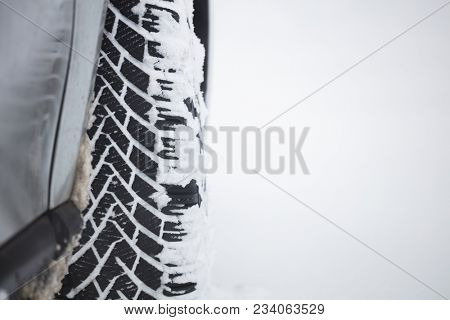 White snow on car' s wheel tire, snowy background, space for text.