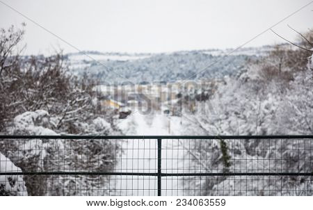 Christmas or winter concept. Snowy distant view of village from balcony. Blurred nature and houses background.
