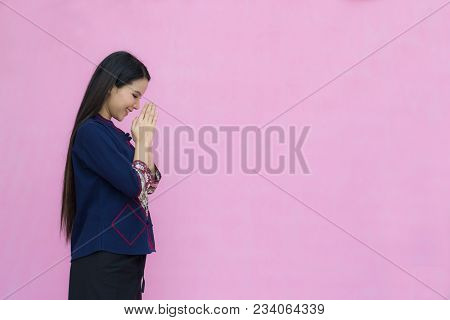 Portrait Of Asian Youn Girl In Traditional Thai Dress Praying Isolated On Pink Background. Wai Sawat