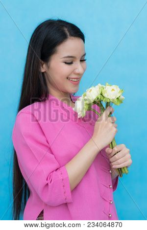 Portrait Beautiful Asian Girl In Traditional Thai Dress And Holding White Lotus Isolated On Blue Sky