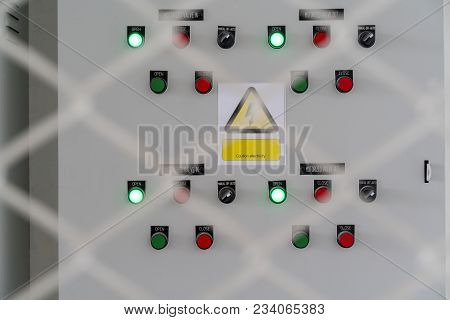Electric City Control Panel In Grey Metal Box Hanging On Wall Inside Chain Link Fence Cage. Electric