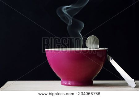 Red Bowl Of Hot Soup With Smoke On Black Background