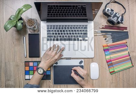 Top View Of Man Designer Using Laptop Computer And Graphics Tablet At Home Office. Professional Occu