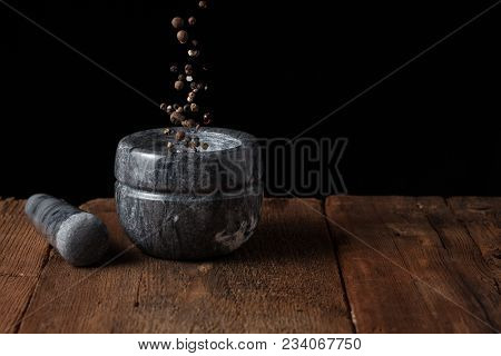 Marble Mortar On Old Wooden Table On Black Background With Copy Space. Pepper Seeds Fall Into The Mo