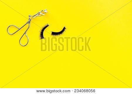 Curled And Thick Eyelashes. False Eyelashes And Eyelash Curler On Yellow Background Top View.