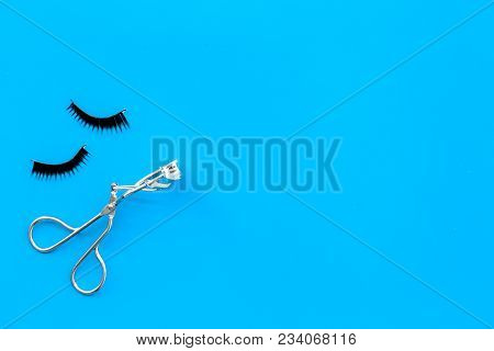 Curled and thick eyelashes. False eyelashes and eyelash curler on blue background top view. poster