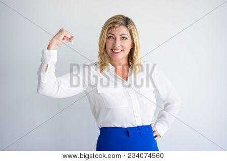 Smiling Mature Caucasian Woman In Formal Blouse Flexing Bicep. Positive Experienced Businesswoman Or