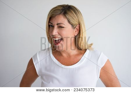 Closeup Of Joyful Middle Aged Woman Smiling With Open Mouth And Winking At Camera. Content Consumer