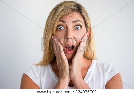 Shocked Mature Caucasian Woman With Open Mouth Covering Cheeks With Hands. Client Discovering Losses