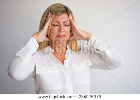 Upset mature Caucasian woman with closed eyes and pain grimace touching head. Female office worker getting bad news or suffering from headache. Business, headache or bad news concept. poster