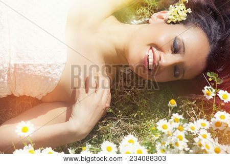 Smiling Harmony Woman Lying On Grass With Daisies. Lights Risers. Beautiful Caucasian Woman With A B