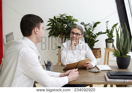 Candid Shot Of Attractive Positive Middle Aged Female Ceo In Eyeglasses Making Notes In Copybook, Li