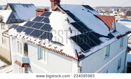 Solar Panels On The Roof Of The House After A Heavy Snowfall In The Winter. Top View