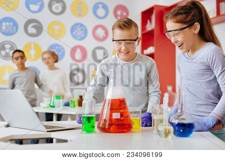 Desirable Reaction. Cheerful Excited Schoolchildren In Safety Glasses Observing The Chemical Reactio