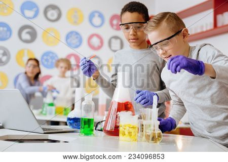 Experimenting With Chemicals. Two Upbeat Teenage Friends Using Pipette And Adding Some Chemical Agen