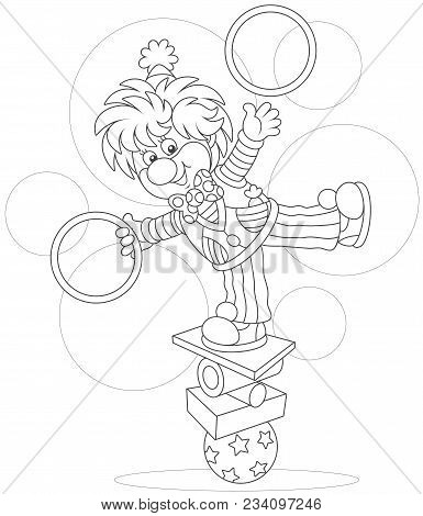 Circus Show Of A Comic Juggler - Equilibrist. Friendly Smiling Clown Balancing On Several Objects An