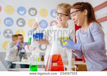 Right Reaction. Two Cheerful Teenage Schoolgirls Holding Flasks With Chemical Substances And Checkin