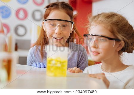 Fascinating Chemical Reaction. Cheerful Teenage Female Students Squatting Near The Table And Watchin