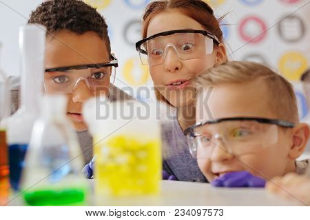 Miraculous Chemistry. Three Upbeat Teenage Students Being Gathered Around The Table And Watching The