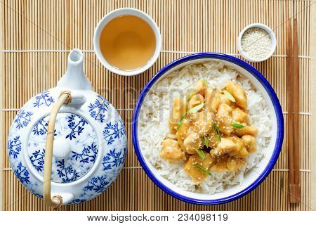 Chinese Orange Chicken With Rice, China Teapot And Cup Of Green Tea On Bamboo Background. Top View.