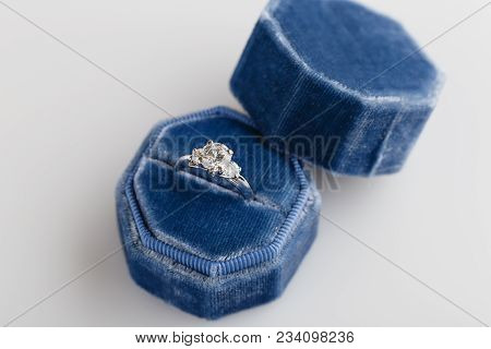 White Golden Wedding Ring With Diamonds In Blue Vintage Velvet Ring Box On White Background. Silver