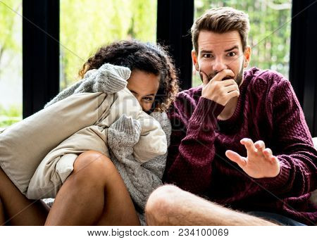 Young couple watching scary movie together