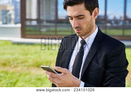 Young manager or agent in formalwear messaging in smartphone while communicating throuigh messenger