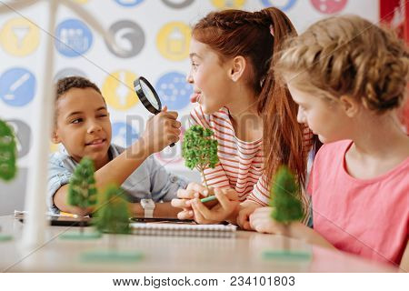 Playful Mood. Upbeat Teenage Girl Holding A Tree Model And Putting Out Her Tongue At Her Classmate W