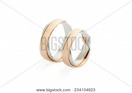 Two White And Rose Gold Wedding Rings Isolated On White Background. Silver And Gold Rings Intertwine