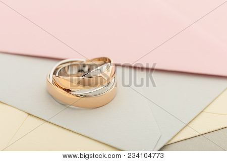 Two White And Rose Gold Wedding Rings On Pastel Envelopes Background. Silver And Gold Rings. Wedding