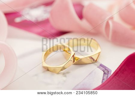 Golden Wedding Rings On Pastel Background With Pink Ribbons. Wedding Invitation Concept