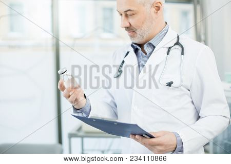 Aged clinician in whitecoat holding clipboard in one hand and looking at bottle with liquid medicine in the other one poster