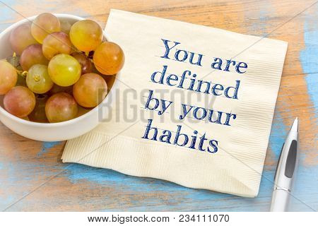 you are defined by your habits - inspirational handwriting on a napkin with some grapes