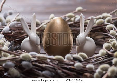 Golden Easter Egg And Rabbits In Catkins Nest On Table