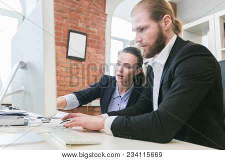 Two business people using computer together in office pointing at monitor
