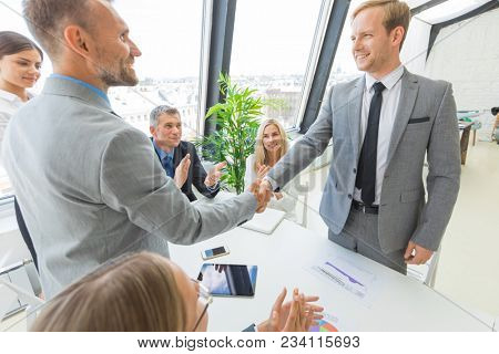Handshake at business meeting in office, people on background applauding