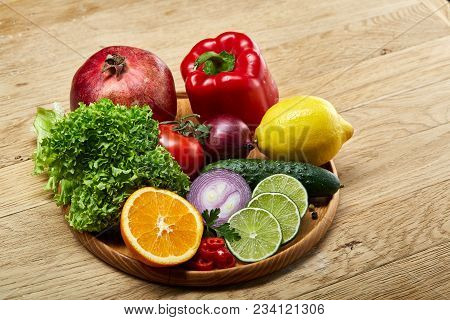 Colorful Still Life Of Fresh Organic Fruits And Vegetables On Wooden Plate Over Rustic Wooden Backgr