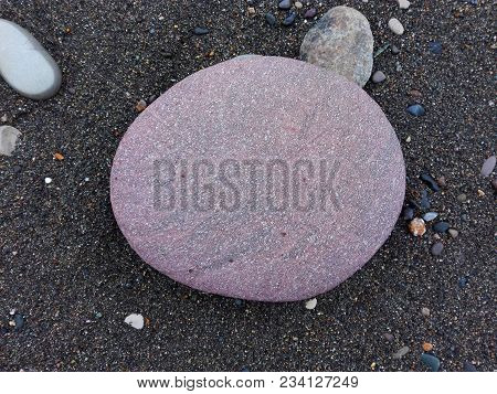 Big Pink Sea Pebble Stone Or Rock In Circle Shape As Frame On Sandy Beach. Pebble Stone Natural Abst