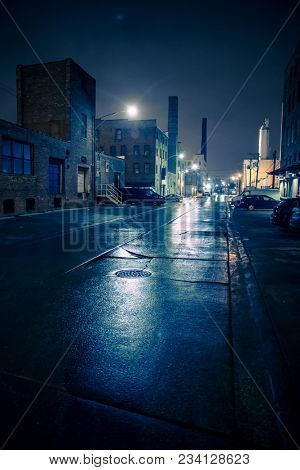 Foggy industrial urban street city night scenery in Chicago with vintage warehouses, factories and smokestacks after a rain. poster