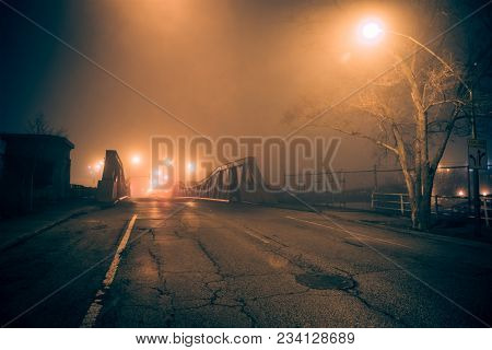 Dramatic industrial vintage river road bridge street scene at night with illuminating fog in Chicago