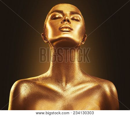 Fashion art Golden skin Woman face portrait closeup. Model girl with holiday golden Glamour shiny professional makeup. Gold jewellery, jewelry, accessories. Beauty gold metallic body, Lips and Skin.