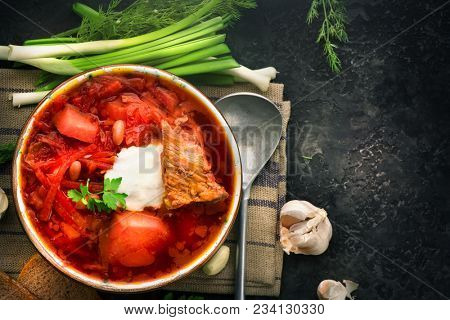 Traditional Ukrainian Russian borscht with white beans on the bowl. Plate of red beet root soup borsch on black rustick table. Beetroot soup Top view. Traditional Ukraine food cuisine