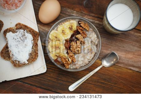 Breakfast With Granola Bowl, Muesli With Oats, Nuts And Dried Fruit, Milk, On Wooden Table. Bannana,