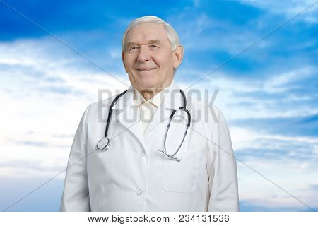 Senior Doctor Against Blue Sky Background. Smilng Old Man Working As Doctor Wearing Stethoscope.