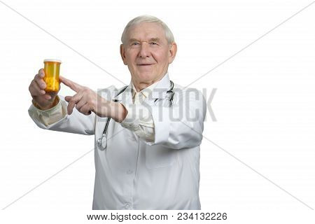 Senior Doctor Pointing At Can Of Pills. Old Physician, Bottle Of Pills Advertisement. White Isolated